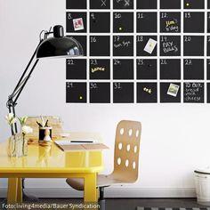 Organisation mal anders: Statt dem herkömmlichen Wandkalender zum Umklappen wurde hier mit Tafelfarbe ein Kalender an die Wand gemalt, der die terminliche Organisation nicht nur einfacher, sondern auch wesentlich schöner macht. Eine Kombi aus knallgelbem Schreibtisch und klassischer Gelenkleuchte in Schwarz rückt den selbstgemachten Tafelkalender in ein modernes Licht.