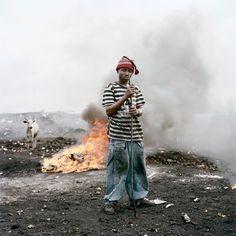3.This photo by Pieter Hugo is of a young man named Ibrahim Sulley, from Agbogbloshie Ghana, 2009. From his series of photos called Permanent Error. In the background there is a cow which once lived in this field and survived off the land, the animal has returned and still feeds off the ground, only now it is littered and poisoned. The fire behind him is constantly burning as both him and the animal breath in the toxic fumes.