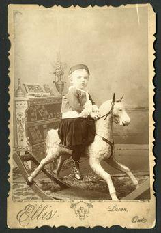 Vintage photo, little boy on a rocking horse