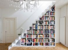 White Bookshelf Staircase This clinically white staircase fully utilizes the otherwise empty void beneath to provide a smart storage solutio...