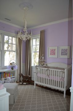 Beige and Lavender Nursery complete with rocking horse, white crib, Restoration Hardware bedding, Pottery Barn Kids rug, Pottery Barn drapes, sheep mobile, bookshelf, chandelier, baskets, and wainscoting.