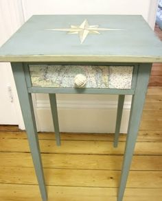 The compass rose on the table top adds so much interest. To secure the map to the drawer front, she used Decoupage Medium, then she also replaced the original drawer pull with a monkey fist. A completely nautical table makeover, transforming a dull side table into a coastal gem.