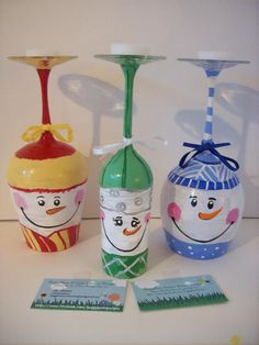 3 adorable snowmen painted on upside down wine glasses with candles at the top and ribbons at the bottom! They can all be used as candle holders! A cute way to bring some fun decor to your home : ) http://www.facebook.com/buggybeandesigns