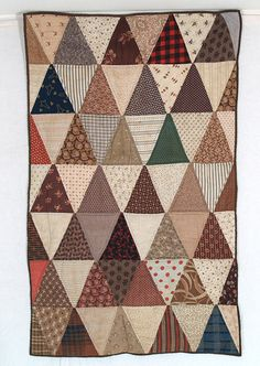 Triangles doll quilt c.1870   25 x 38 -- The 5 x 6 x 6 triangles in shades of brown and taupe could quite possibly be made from Cocheco Mill fabrics. Backed with a fabulous c.1840 brown vermiculated stripe