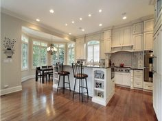 Elegance White Kitchen Cabinets Design With Black Granite Countertops For Big Kitchens Layout With Modern Chrome Kitchen Island Ideas And Inspiring Marble Top Dining Table Set Design