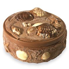"Milk chocolate box covered with cinnamon and sugar with milk, dark and white chocolate accents. Box size: 8"" diameter x 2 1/2"" height (add extra 1 1/2"" height and 1/2"" width for chocolate seashells)."