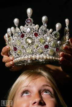 A Christie's employee looks up at a diamond, ruby, and pearl crown in London in 2005. The crown is set with 1,000 carats of white and yellow diamonds and was expected to fetch between 2.3 million and 3.3 million pounds at auction.