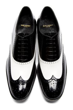 Black & White Leather University Richelieu Spectator Shoes by Saint Laurent. Low-top buffed leather spectator shoes in black and white. Wingtip paneling and broguing accents throughout. Round toe. Black oxford-style lace-up closure. Tonal sole and stitching. http://zocko.it/LDCBd