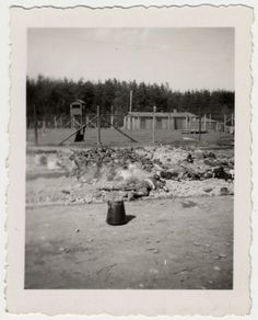 """Bodies and bones of dead prisoners lie piled near the fence of the Landsberg concentration camp. The original caption reads: """"Dead burning Jews of concentration camp in Landsberg, Germany"""". [Photograph #71955] Date:Sunday, April 29, 1945 - Wednesday, May 02, 1945  Locale:Landsberg, [Bavaria] Germany  Credit:United States Holocaust Memorial Museum, courtesy of Albright College  Copyright:United States Holocaust Memorial Museum"""