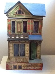 antique printed paper dolls house with blue roof & metal fireplace. 42cm high