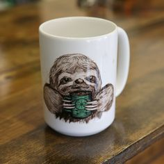 Sloth sipping coffee mug! Our newest addition to our housewares collection; animals sipping coffee on mugs! Our exclusive design on this 16oz mug to make your home rad.