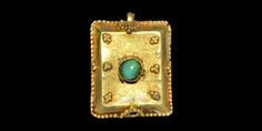 BYZANTINE GOLD FILIGREE PENDANT WITH TURQUOISE CABOCHON 6th-8th century AD  A hollow rectangular fabricated pendant with chamfered sides, granulation to the border; triangular granule details to the sides and upper face, central cell with turquoise cabochon; recess to the lower face for attachment of a second element. 1.30 grams, 17 mm