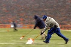 Employees clean the field lines of snow during a game between the New England Patriots and the Denver Broncos at Sports Authority Field at Mile High on November 29, 2015 in Denver, Colorado.