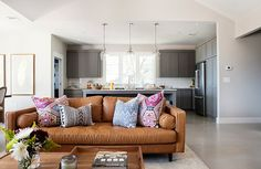 modern camel leather sofa, moroccan patterned pillows, stained concrete floors, Sherwin Williams gauntly gray kitchen cabinets, Sherwin Williams worldly gray walls