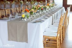 Long tables with collected vases of flowers on a burlap runner
