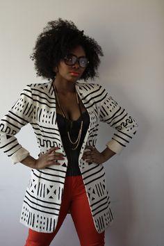 Big hair + large black eyeglasses + black & white print blazer + long black & gold necklace
