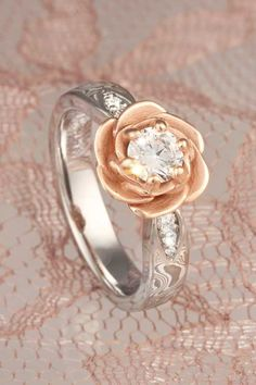 A blossoming rose cradles the center diamond or sapphire in this floral engagement ring. The rose is planted on a band of mokume gane, with 0.09 ctw diamond accents in leave-shaped recesses. This design is a great choice for modest-sized center stones, but can also be scaled up for larger stones.