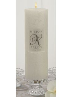 Scroll Pattern Wedding Unity Candle made of solid wax available in white or ivory.  It is embossed with a scroll pattern featuring vines and leaves. The center of the candle has a debossed rectangle that can be personalized.