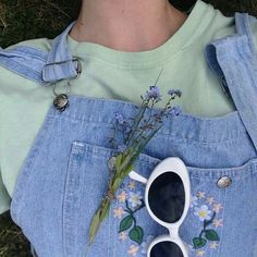 a photo of someone wearing a green shirt and denim overalls with flowers and a pair of white sunglasses in the front pocket