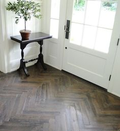 "Herringbone Hardwood Floor. Entry Herringbone Hardwood Floor Ideas. The wood flooring throughout the house is French oak, with a custom finish. We chose a herringbone pattern in the entry, dining room, library and guest cottage and 11"" wide planks through"