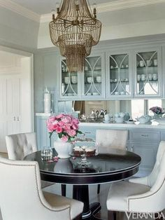 Colors -- Light Blue, Espresso, White, Gold (and coral accent vs flowers) --- Turquoise blue dining room design with gray blue cabinets, round black pedestal dining table with white trim, cream tufted chairs with nailhead trim and gorgeous mesh chandelier.