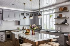 Gorgeous gray kitchen features a honey stained island fitted with a microwave positioned beneath a white marble countertop holding a farmhouse sink with a polished nickel deck mount hook and spout faucet lit by three Small Hicks Pendants hung from a gray shiplap ceiling.