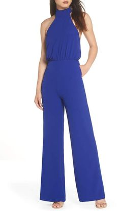 A high mock-neck collar balances the open back of a wide-leg jumpsuit with minimalist chic. A bit of blousing at the bodice softens the sleek silhouette. Jumpsuit For Wedding Guest, Best Wedding Guest Dresses, Jumpsuit Dressy, Halter Jumpsuit, 60s Fashion Trends, Minimalist Fashion Women, Minimalist Chic, Classy Outfits, Jumpsuits For Women
