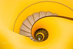 Vortex - Earlier today, I discovered this fantastic, yellow and vertigo-inducing spiral staircase in a Geneva parking garage. It reminded me of beautiful stuff by Gaudi and Hundertwasser. I spent 20 good minutes rigging my camera gear and making the necessary adjustments to get the final picture right. Luckily, all the shops were closed, so I was pretty much alone in the entire building.