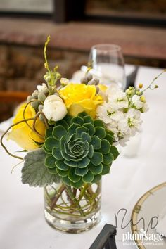 Charming centerpiece by Plum Sage Flowers featuring: succulents, white ranunculus, stock, curly willow, silver brunia, dusty miller and yellow roses.