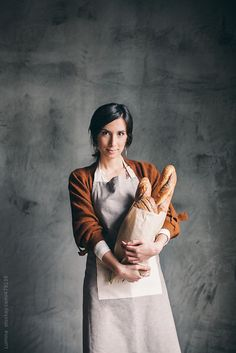 A COMEREM UMA FATIA: Portrait of a bakery employee holding a bag full of bread.