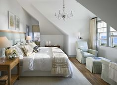 Master in the attic. Beautiful attic master bedroom with wood floor, white carpet rug and sitting area.