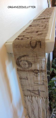 Make a burlap mantel scarf or runner out of a Christmas garland. Would be fun to make a christmas garland like this with stamped holiday sayings or words.