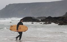 James Otter walking out of the sea carrying a wooden mini simmons hull surfboard