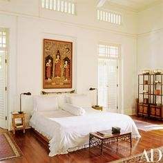 A rare early-20th-century Thai painting of Buddha and two disciples hangs above the bed in the master bedroom | archdigest.com