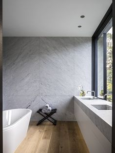 Tobias Partners - Cooper Park House. In the main bathroom, Kaldewei 'Centro Duo' bath from Candana. Vola taps, 'Bazane' stool from Christian Liaigre. Walls are covered in imported marble.