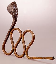 Brass & copper serpentine horn (nagfani), from Gujarat or Rajasthan, India. 20th century. Associated with Lord Shiva & used by holy men (sadhus) during ritual ceremonies, also by story tellers and street performers.