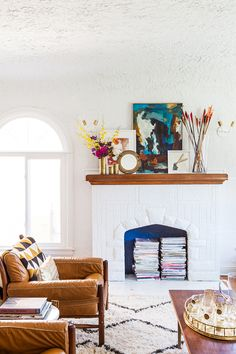 White fireplace with warm wood mantel styled with abstract art, gold vases, flowers, and colorful arrows.
