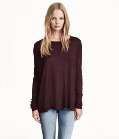 Oversize-Pullover aus Feinstrick mit langem Arm, überschnittenen Schultern und weitem Halsausschnitt. Breite gerippte Ärmelbündchen. Seitliche Schlitze und etwas länger geschnittenes Rückenteil.