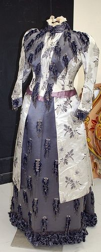 Afternoon maternity dress by Emile Pingat, 1880s. The bodice had been altered significantly to accommodate a larger bust, but there had been no alteration to the piping around the bottom of the bodice, suggesting that the alterations were done by the maker. There are no alterations to the skirt. Given the manner in which the dress wanted to drape, we're wondering if this was a very fancy maternity dress made for a particular event.