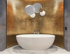 Wrapped in the comforting patina of a metallic panel, the tub has an otherworldly atmosphere perfect for washing away the worries of the day. Above, circular pendant lamps bring to mind images of playful bubbles or pristine moons.