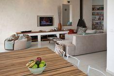 ספות בהירות, פוף שנתפר בהזמנה מיוחדת בהתאם לצבעים שנבחרו לבית, ''מזנון'' בנוי מבטון ושולחן קפה שנמצא הרוס ושופץ (צילום: גידי בועז)