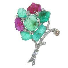 "Rare Multi Gem & Diamond ""Tutti Frutti"" Flower Brooch  AMERICAN  1930'S  A carved emerald and ruby diamond brooch from the art deco period. Diamond weighing aprox 2.20 carats, emeralds aprox 38 carats and rubies weighing aprox 9 carats. Set on platinum."