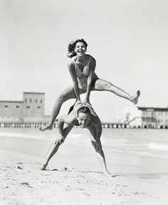 A couple playing leapfrog on a beach in the 1940s