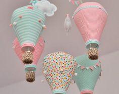 Hot air balloon mobile pour bébé en tissus vert menthe, gris et blanc. Chaque ballon est fabriqué à partir de tissus et orné de boutons, pompons, dentelle, rubans, nœuds, guirlande de fanions et mini-hand paniers fait au crochet. Ballons et feutre gonflé nuages pendent de mobile en bois. Vous pouvez personnaliser un des nuages avec le nom ou date de naissance maintenant ou plus tard.   MESURE ENVIRON :  -Ballon (avec panier) 22 cm x 12 cm (8,6 x 4,7) -Panier 3,5 cm x 2,5 cm (1,3 x 0,9)…