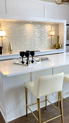 Glam snack bar with molding and glass mosaic tile, white and gold stools and circular seating area.  Click to see more model home design ideas and learn how to decorate your own home... THE DECORATING COACH  #gameroom
