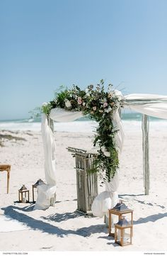 An arch built using bare sticks, was ornamented with swathes of white material and a luscious arrangement of foliage and flowers. | Photographer: Yolandé Marx | Florist: Studio Bloem