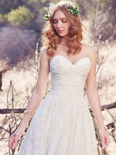 Maggie Sottero - MARTA, This vintage-inspired wedding dress features a ruched bodice, allover lace, and sheer pockets at the hip. A strapless sweetheart neckline and scalloped lace hemline evoke soft glamour. A-line lined with Viva Jersey for a luxe feel. Finished with covered buttons over zipper and inner elastic closure.