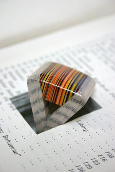 Artist Jeremy May makes jewelry by carving shapes out of books and laminating them.