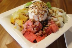"""""""Patbingsu, or patbingsoo, is a popular dessert in South Korea.  This snack originally began as ice shavings and sweetened azuki beans (known as pat) and was sold by street vendors. In contemporary culture, it has become a very elaborate summer dessert, often topped with ice cream or frozen yogurt, sweetened condensed milk, fruit syrups, various fruits such as strawberries, kiwifruit, and bananas, small pieces of tteok (rice cake), chewy jelly bits, and cereal flakes."""""""