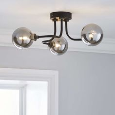 Designed with three black curved arms, this ceiling light fitting features three shiny glass spheres which change colour when the light is switched on. Lounge Lighting, Hall Lighting, Flush Lighting, Lounge Ceiling Lights, Ceiling Lamps, Bathroom Light Fittings, Bathroom Ceiling Light, Bathroom Lighting, Light Fixtures
